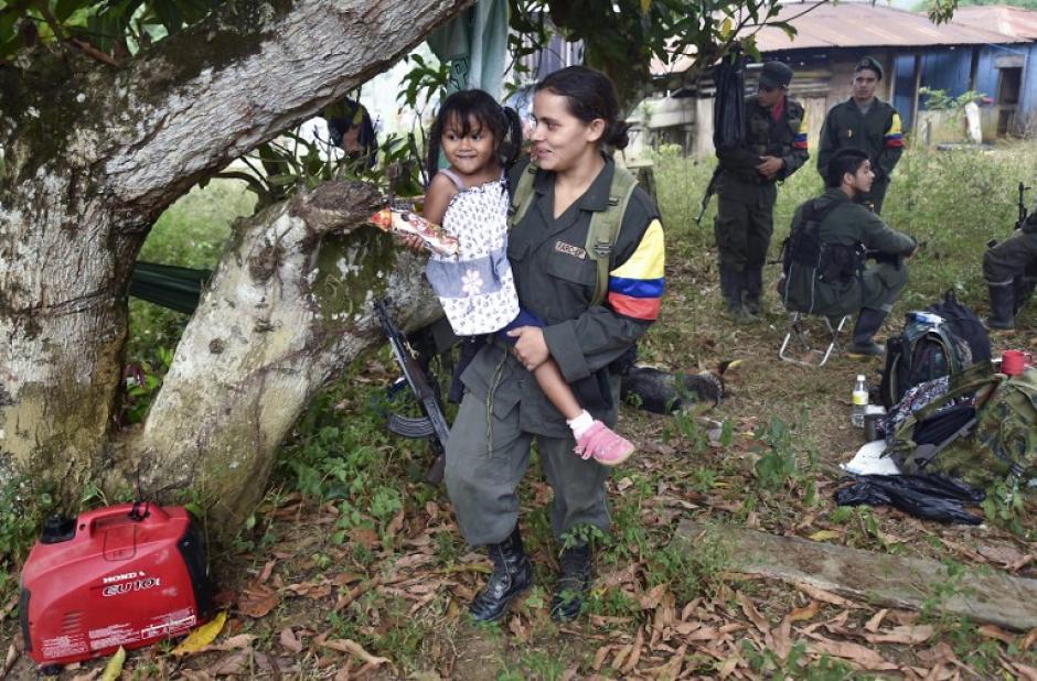 Una mujer insurgente sostiene a la hija de uno de sus compañeros durante una visita familiar al campamento. (Foto: AFP)