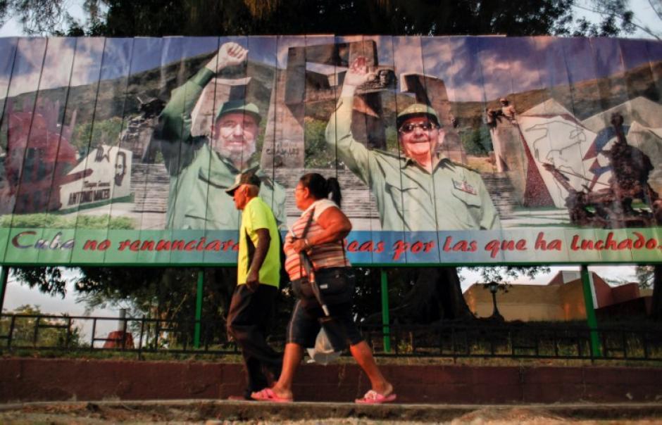 Una pareja pasa frente a uno de los murales que hay en La Habana. (Foto: AFP)
