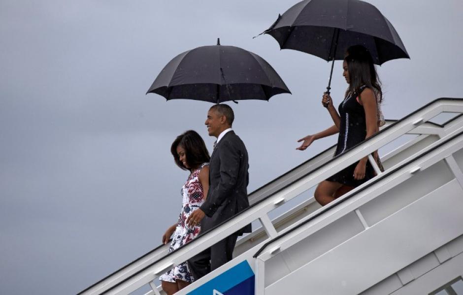 Obama y su familia bajaron del avión presidencial en medio de la lluvia. (Foto: AFP)