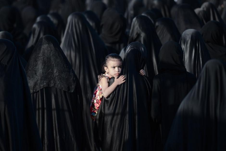 Una niña de Bahréin es llevada por su madre durante el funeral de Sayed Omran Hameed Sayed, el 28 de mayo de 2013, en el pueblo de Karzakkan, al sur de Manama. Hameed, de 26, murió en el hospital después de desarrollar complicaciones respiratorias y sus familiares afirman que su muerte se debe a la inhalación de gases lacrimógenos tóxicos que la policía antidisturbios utilizó durante una protesta en mayo de 2013.(Foto: AFP/MOHAMMED AL-SHAIKH)