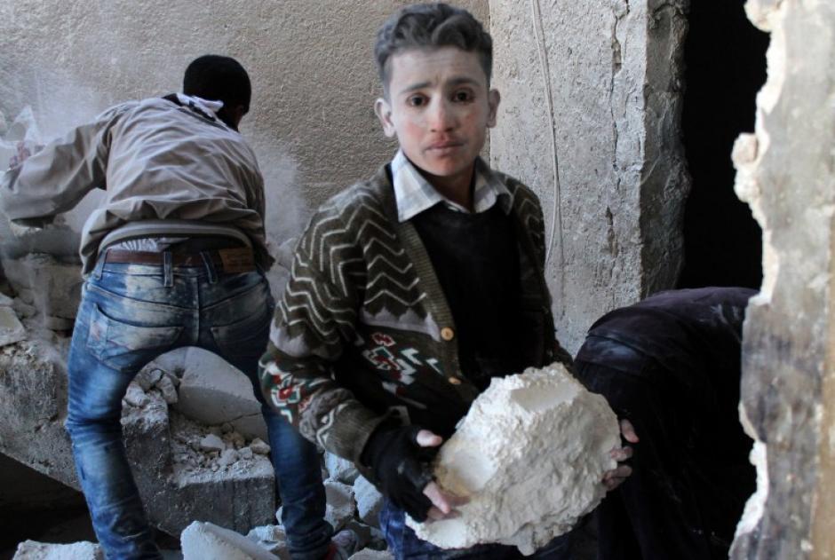 Un jovencito sirio ayuda a descombrar una vivienda en un barrio bombardeado por fuerzas opositoras. Foto AFP