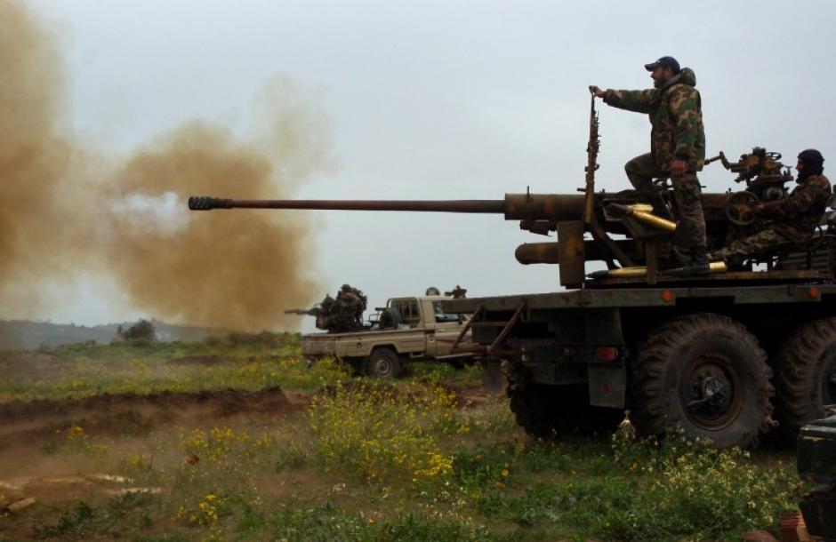 Las fuerzas sirias disparan un cañón y una ametralladora pesada carga en un camión durante los combates contra los rebeldes en la ciudad de Zara, en la provincia de Homs, el 8 de marzo de 2014. Las fuerzas sirias capturaron hoy la ciudad controlada por los rebeldes de Zara cerca de un castillo cruzado famoso en la provincia estratégica de Homs, después de casi un mes de combates, dijo el ejército. (Foto: AFP / STR)