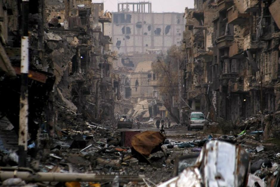 Una imagen tomada el 04 de enero 2014 muestra a sirios caminando por una carretera severamente dañado en la ciudad nororiental de Deir Ezzor. Lo peor del conflicto es que no se ve que el final esté próximo. (Foto:AFP/AHMAD ABOUD)