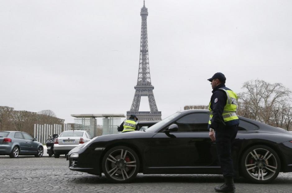 Oficiales de policía controlan la circulación de autos frente de la Torre Eiffel, se permite la circulación de vehículos con placas que terminen en número impar. (Foto:AFP)