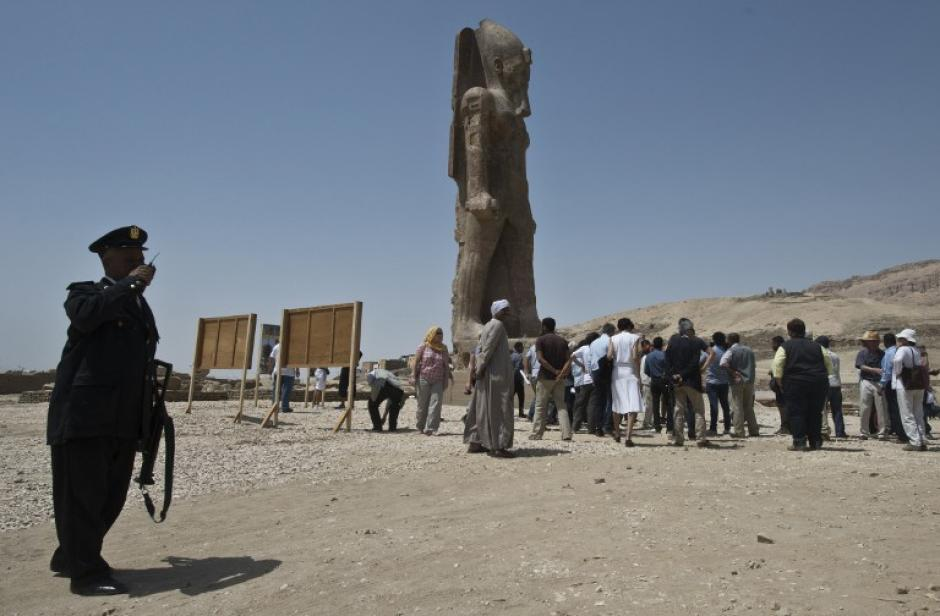 Turistas y periodistas admiran una de las enormes estatuas del faraón Amenofis III en la ciudad templo de Luxor en Egipto. (Foto: AFP)