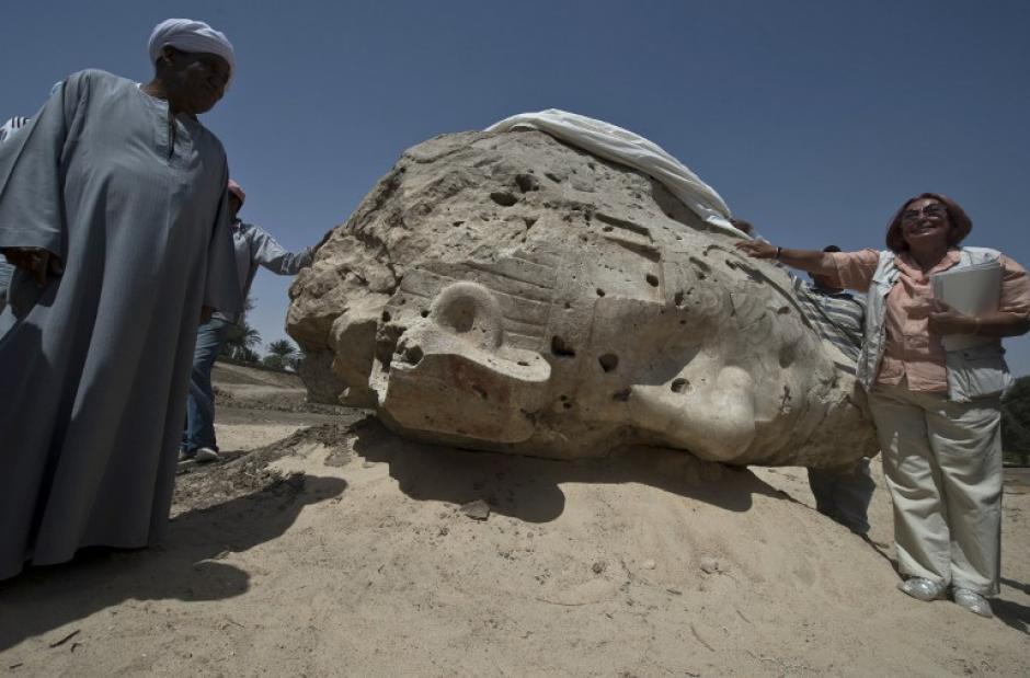 La arqueóloga alemana Hourig Sourouzian, quien dirige la exploración del templo de Amenofis III, posa al lado del más reciente hallazgo de la cultura egipcia. La alemana está parada al lado de una enorme cabeza de alabastro de la estatua del rey Amenofis III en Luxor, Egipto. (Foto: AFP)