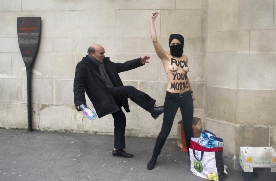 Un hombre patea a una activista en topless del movimiento feminista ucraniano Femen mientras levanta el puño para protestar contra los islamistas frente a la Gran Mezquita de París el 3 de abril de 2013. AFP PHOTO / FRED DUFOUR