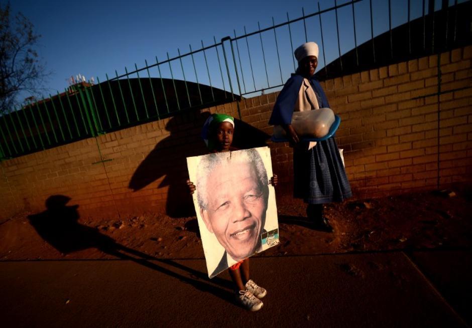 Una mujer y una niña portan una imagen Nelson Mandela frente al hospital del corazón Mediclinic en Pretoria el 3 de julio de 2013. Multitudes emocionales se reunieron frente al hospital donde Nelson Mandela estaba en condición crítica antes de su deceso en noviembre. Foto:AFP/ Filippo MONTEFORTE)