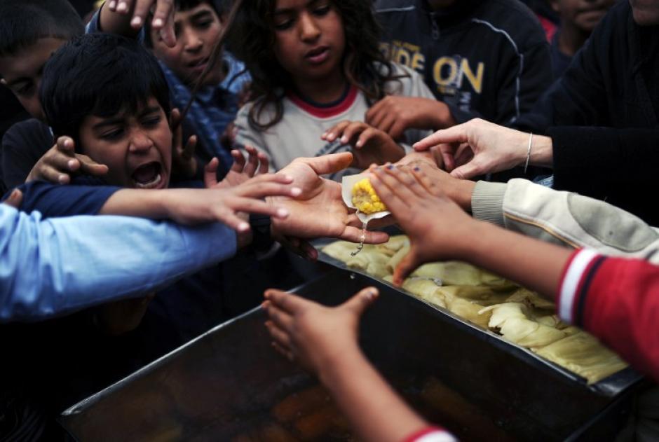 Un niño refugiado de la etnia yrian intenta tomar un un trozo de comida, en un parque donde habita junto con otras 600 mil personas, que huyeron de la guerra en Siria o fueron desplazados, hacia Estambul Turquía, país que comparte 900 kilómetros de frontera de Siria un país en conflicto armado. (KILIC BULENT/AFP)