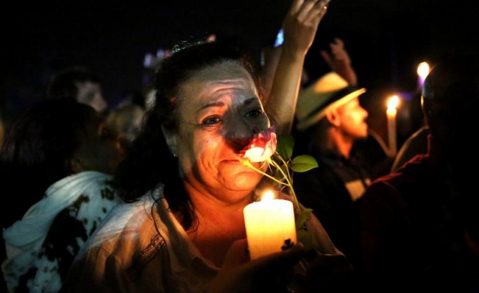 El mundo esta de luto por la muerte de Nelson Mandela, pilar de la lucha anti racista y el apartheid en Sudáfrica. En la foto una mujer sostiene una vela y una rosa fuera de la casa del ex presidente el 5 de diciembre, fotografía tomada por Alexander Joe de AFP.