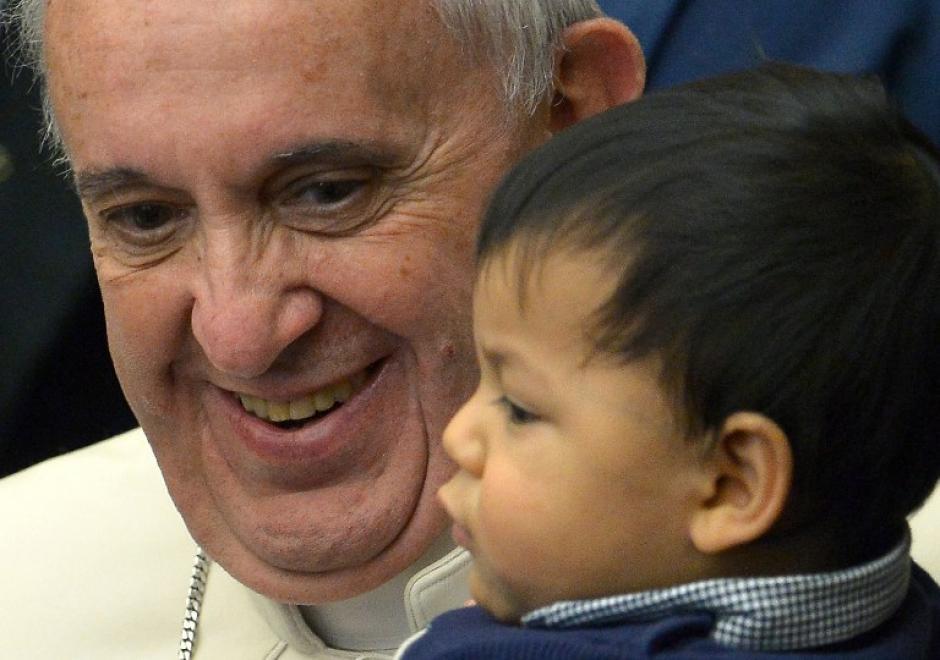 El momento en que el Papa carga a uno de los niños del dispensario. Foto AFP