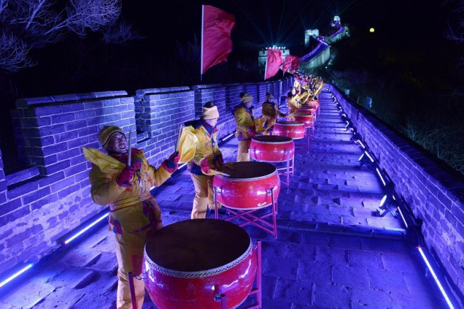 Personas vestidas con trajes tradicionales realizan un espectáculo para recibir el año nuevo en la Gran Muralla China