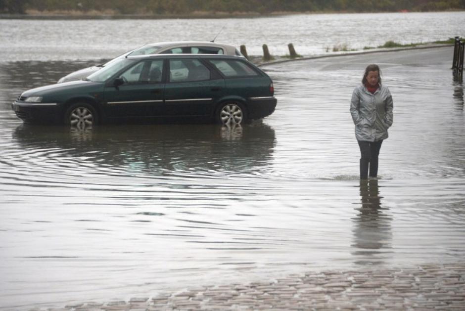 Una mujer camina en una calle inundada del puerto de Saint Goustan en Auray, Bretaña, como siete ríos en el oeste de Francia fueron puestos bajo alerta de inundaciones debido a las fuertes lluvias en la región. AFP PHOTO / DAMIEN MEYER