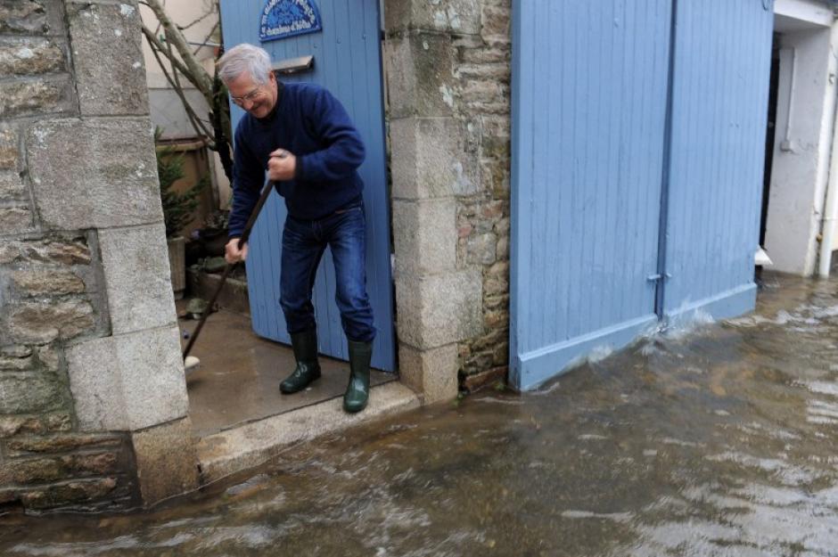 Un hombre limpia la entrada de su casa en Quimperle, oeste de Francia, inundada por el río de Laita. La ciudad está bajo alerta por las fuertes lluvias y al alto oleaje de las mareas. AFP PHOTO / FRED TANNEAU