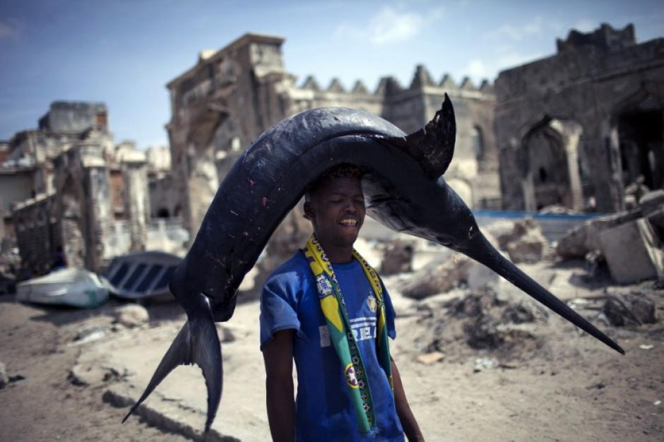 Un pescador de Mogadiscio, este de Somalia, carga un pez espada sobre su cabeza durante la venta en el mercado de la región. Foto AFP