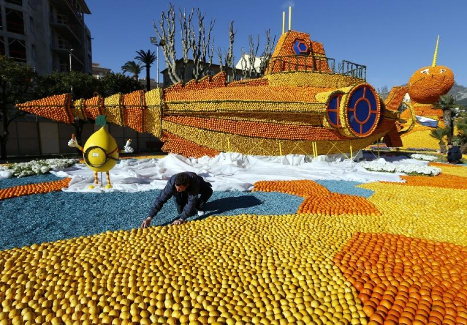 """Un hombre trabaja en una escultura hecha de naranjas y limones el 14 de febrero de 2014 en Menton, en la Riviera francesa, antes del inicio de la """"Fête du Citron"""". El tema de esta 81 edición, desde el 15 de febrero hasta el 05 de marzo 2014, es """"Veinte mil leguas de viaje submarino"""". (Foto: AFP/VALERY HACHE)"""