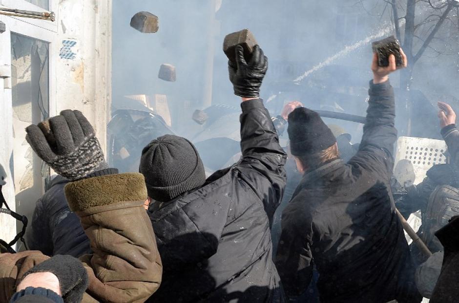 Los manifestantes lanzan piedras al parlamento. Foto AFP