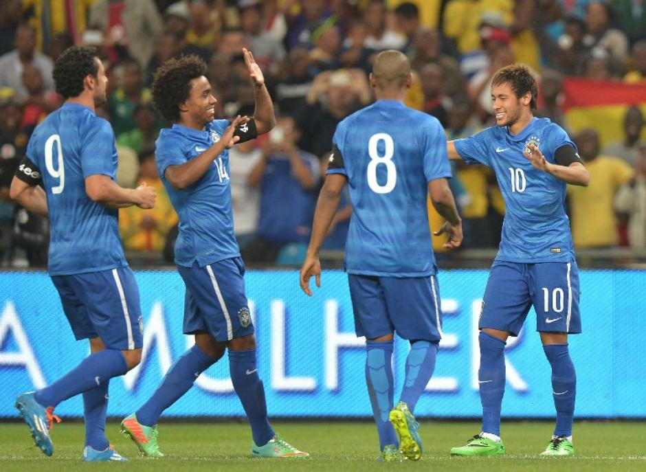 Los seleccionados de Brasil felicitan a Neymar, quien anotó un triplete ante Sudáfrica en Johannesburgo. (Foto: AFP)