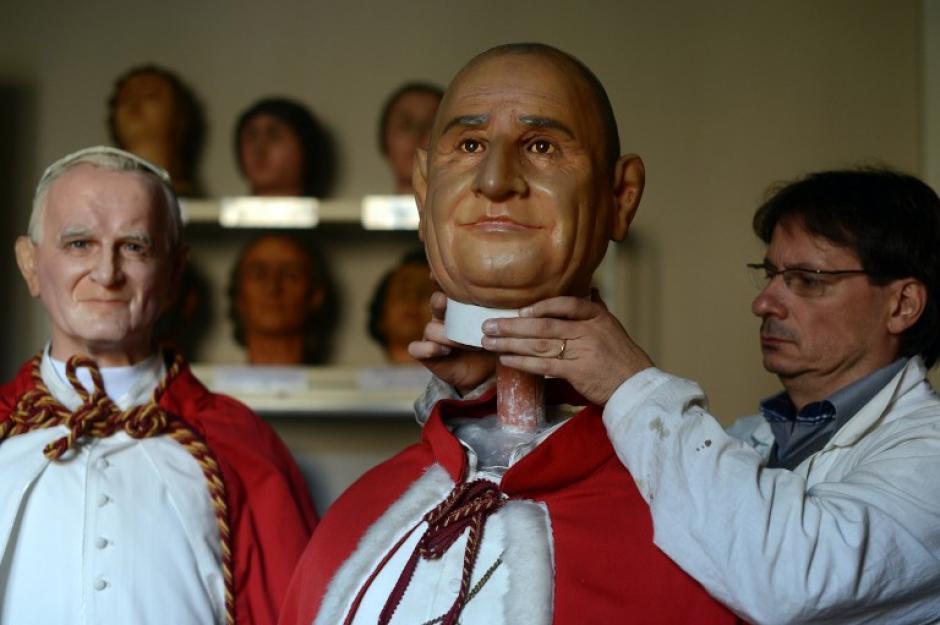 Fernando Canini, director del museo de cera de Roma, le da el toque final a la nueva estatua de cera que representa a los papas Juan Pablo II y de Juan XXIII. (Foto:AFP/ GABRIEL BOUYS)