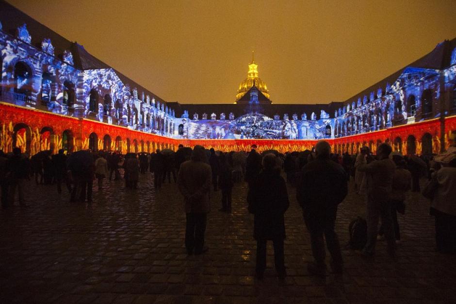 """Cinetos de personas observan un espectáculo de luz y sonido en el patio del Hotel """"Invalides""""en París.(Foto: AFP PHOTO / JOEL SAGET)"""