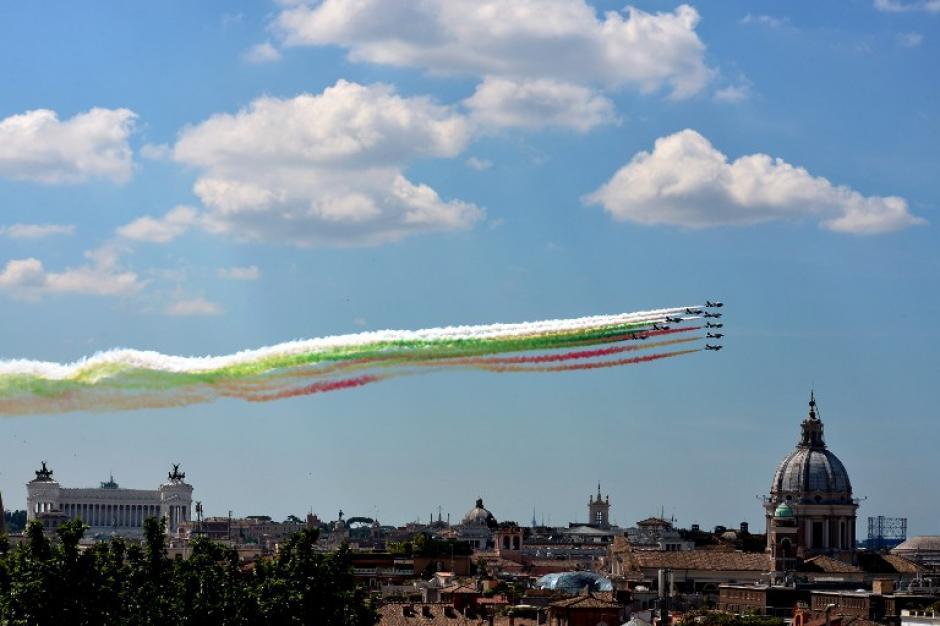 """Aeronaves de la unidad de acrobacia aérea de la fuerza aérea italiana """"Frecce Tricolori"""" dejan estelas de humo con los colores de la bandera nacional de Italia en el monumento a Vittorio Emanuele de Roma. En la foto del 2 de junio de 2014, tomada por Vicenzo Pinto de AFP."""