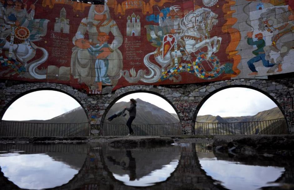 Madre e hija juegan a la orilla de una poza, rodeada de murales que narran la historia del pueblo de Gudauri, ubicado a unos 120 kilómetros de la capital de Georgia. (Foto: Kirill Kudryavtsev/AFP)
