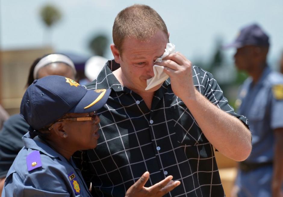 Una agente policial de Sudáfrica brinda consuelo a un ciudadano que observa las honras fúnebres a Nelson Mandela. Foto AFP