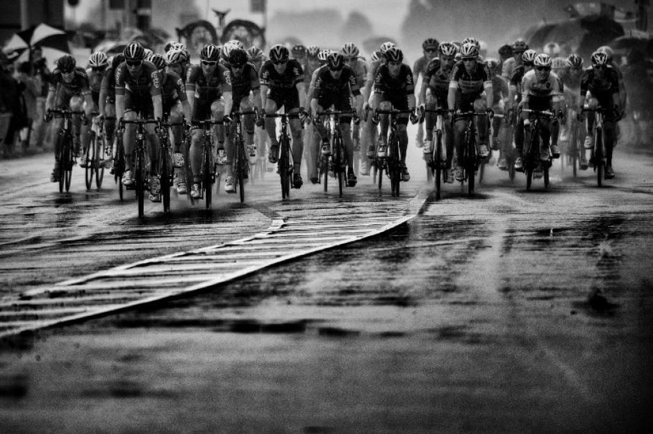 Una imagen del pelotón a toda velocidad sobre el pavimento mojado, durante la segunda etapa del Tour de France. (Foto: Erick Feferberg/AFP)