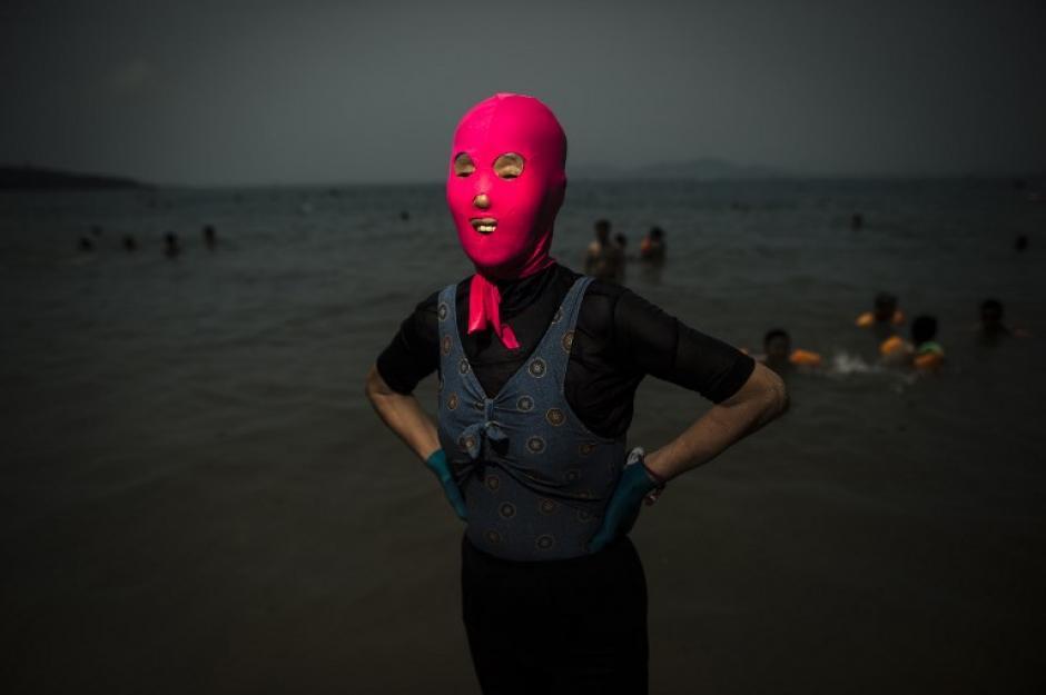 Una mujer que llevaba un facekini pasea por la playa en Qingdao, provincia oriental china de Shandong. (Foto: AFP/Fred Dufour)