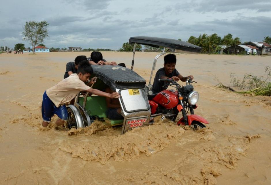 Los residentes empujan un triciclo en una carretera inundada en la ciudad de Santa Rosa, provincia de Nueva Ecija, el 19 de octubre 2015. (Foto: AFP/TED ALJIBE)