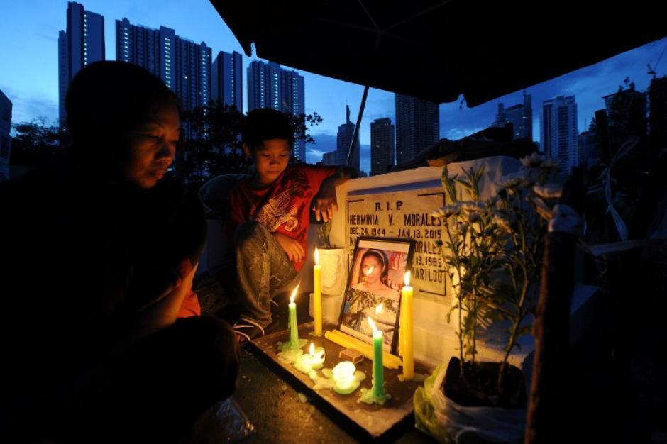 Una mujer, acompañada por su hijo, mantiene vigilia con velas en la tumba de su madre como honran a los muertos en el Día de Todos los Santos en Manila el 1 de noviembre de 2015. (Foto: AFP/ Jay DIRECTO)