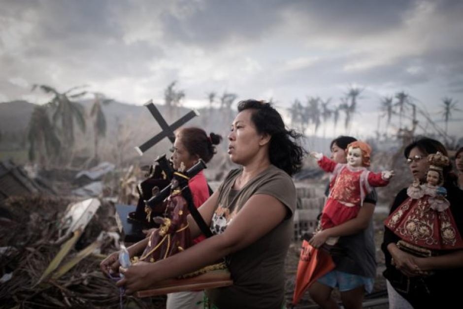 Los sobrevivientes del Tifón Haiyan realizan una procesión de rogativa en Tolosa, en el este de Filipinas en la isla de Leyte. Entre el caos generado por la tragedia estos fieles devotos oran para fortalecer la fe de los afectados y por el alma de las víctimas. Foto: AFP