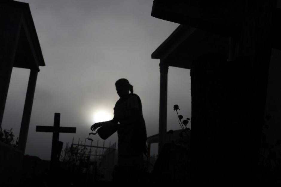 Una mujer limpia una tumba en el cementerio de Tuxtla, estado de Guerrero, México, durante la celebración de Todos los Santos el 1 de noviembre de 2015. (Foto: AFP / Pedro PARDO)