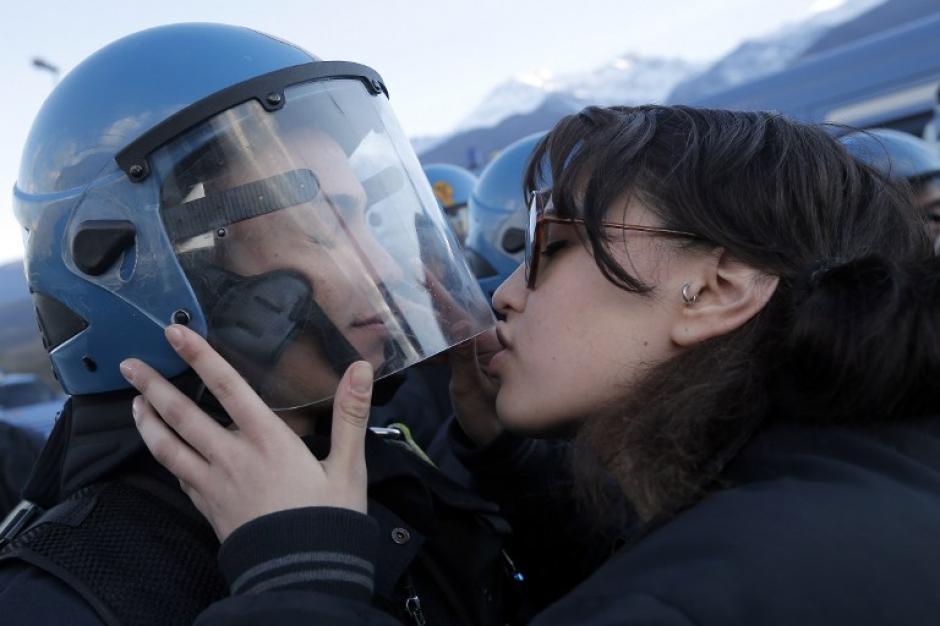 En la foto del día del 18 de noviembre, una manifestante besa inesperadamente a un agente de la policía antidisturbios italiana. La protesta se realizó el fin de semana para evitar la instalación de un tren de alta velocidad entre Lyon, Francia y Turín, Italia. El agente confesó a los medios de comunicación que no lo entrenaron para responder ante esta acción. (Marco Bertorello/AFP)