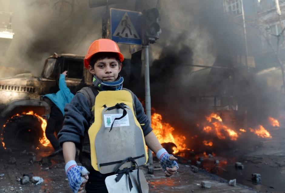 Un niño toma parte de las manifestaciones en Kiev. Al menos 30 personas resultaron heridas y una de ellas con la mano amputada. Foto AFP