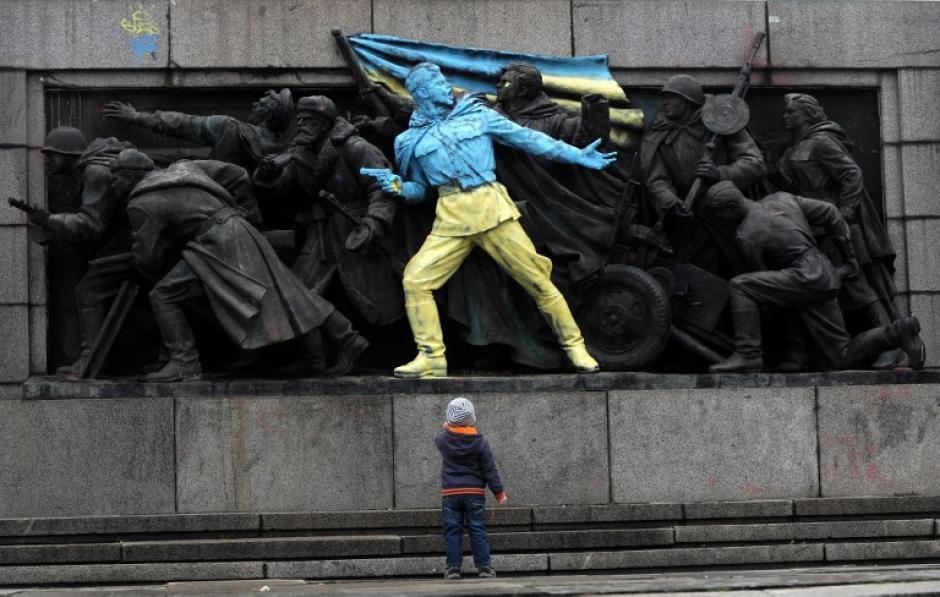 Un niño observa una figura pintada con los colores de Ucrania en el monumento al Ejército Soviético en el centro de la ciudad de Sofía en Bulgaria. El principal monumento al ejército soviético en Sofía amaneció pintado de esa manera como una medida de apoyo a todas las manifestaciones ocurridas en Ucrania en las últimas semanas. (Foto: AFP)