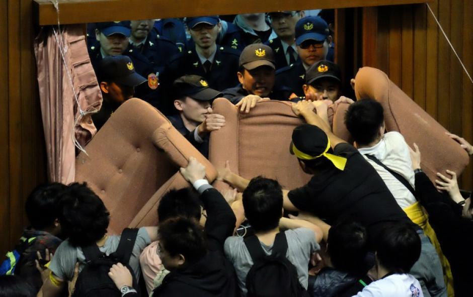 Los agentes de policía tratan de entrar al Parlamento taiwanés que está ocupado por manifestantes. (Foto:AFP)