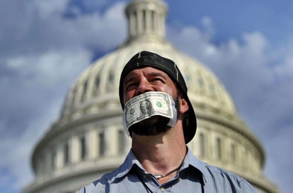 Un manifestante se cubre la boca con un billete de un dólar, en una manifestación en frente del Capitolio de EE.UU. en Washington, DC, instando al Congreso a aprobar la ley de presupuesto. . El presidente Obama criticó a los republicanos por el cierre del gobierno como parte de una cruzada ideológica, diseñada para matar a su ley de la atención sanitaria. El gobierno de EE.UU. cerró el 1 de octubre de 2013, la primera vez en 17 años
