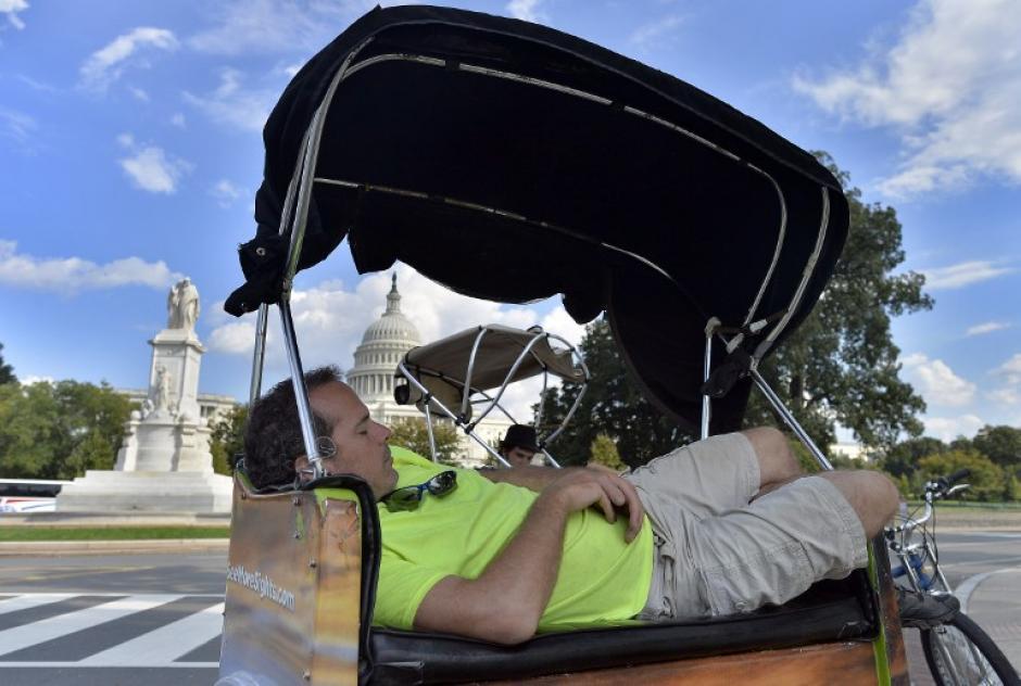 Un conductor de bicitaxi, cuya actividad principal es el transporte de turistas de una atracción a otra en la capital estadounidense, toma una siesta cerca del Capitolio en Washington DC.