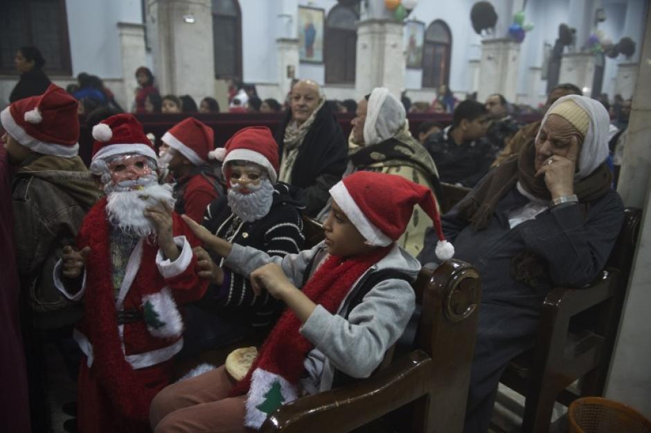 Niños cristianos en el Cairo, acuden al servicio de bendición del Nuevo Año vestidos de Santa Claus. Foto AFP