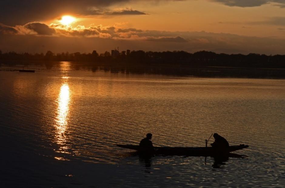 Un pescador en Kashmir, India limpia una red de pesca en el Lago en Srinagar. (Foto: AFP)