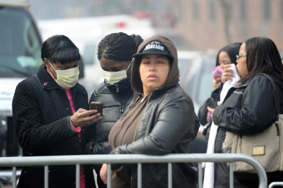 Transeúntes se cubren el rostro con mascarillas y observan el trabajo de los bomberos tras la explosión de este miércoles. (Foto:AFP)