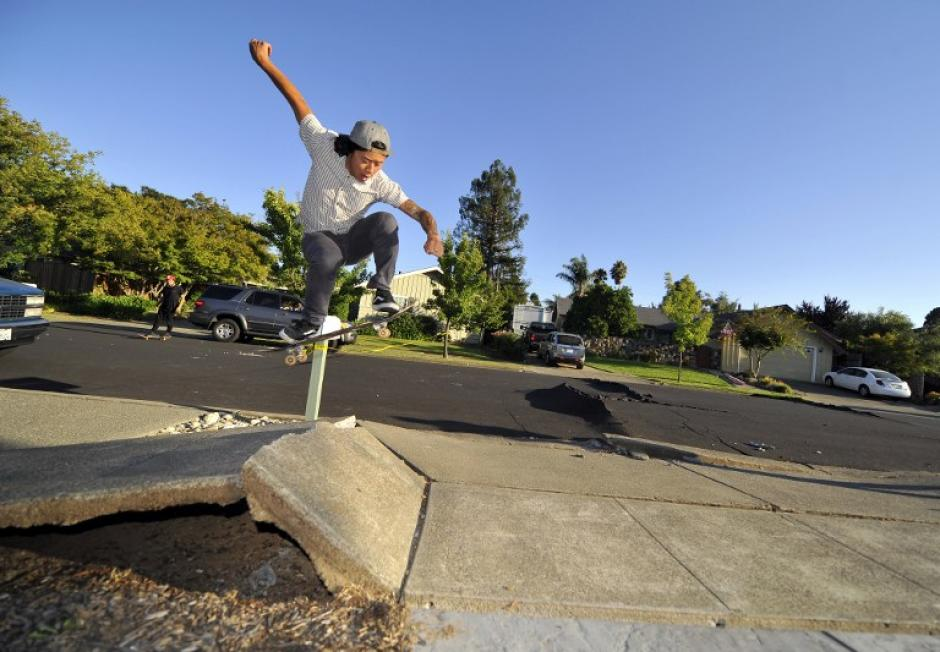 En la imagen aparece Ryan Young haciendo skateboard sobre una banqueta destruida tras el paso del terremoto en la región de Napa, California. (Foto: Josh Edelson/AFP)