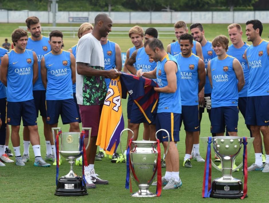 Bryant e Iniesta autografiaron sus camisolas frente a los trofeos conseguidos en la recién finalizada temporada por el Barcelona. (Foto: AFP)