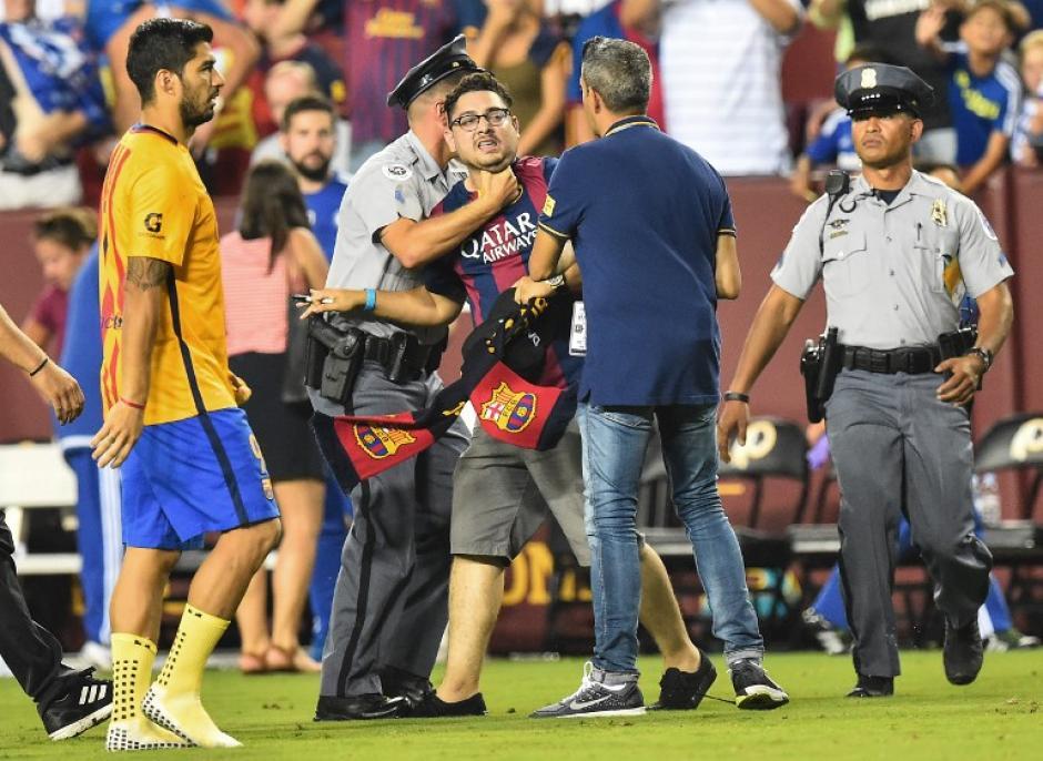 Un aficionado del Barcelona que intentó saludar a los jugadores durante la tanda de penales fue atrapado por los agentes de seguridad. (Foto: AFP)