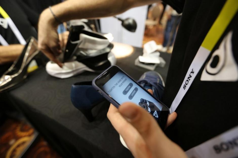 Una aplicación de teléfono inteligente se utiliza para apretar automáticamente losZapatosDigisole en el CES. (Foto: AFP/DAVID McNew)