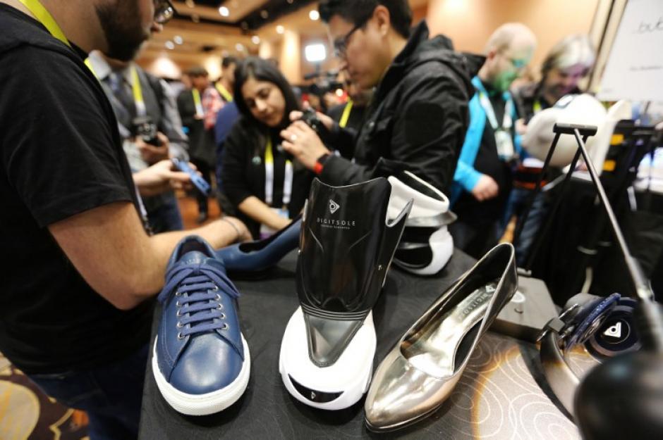 La gente observa los zapatos Digisole que son controlados por una aplicación de teléfono inteligente para diferentes acciones tales como ajuste automático de zapato, el calentamiento del pie, de medición de absorción de impactos y las calorías quemadas. (Foto: AFP/DAVID McNew)