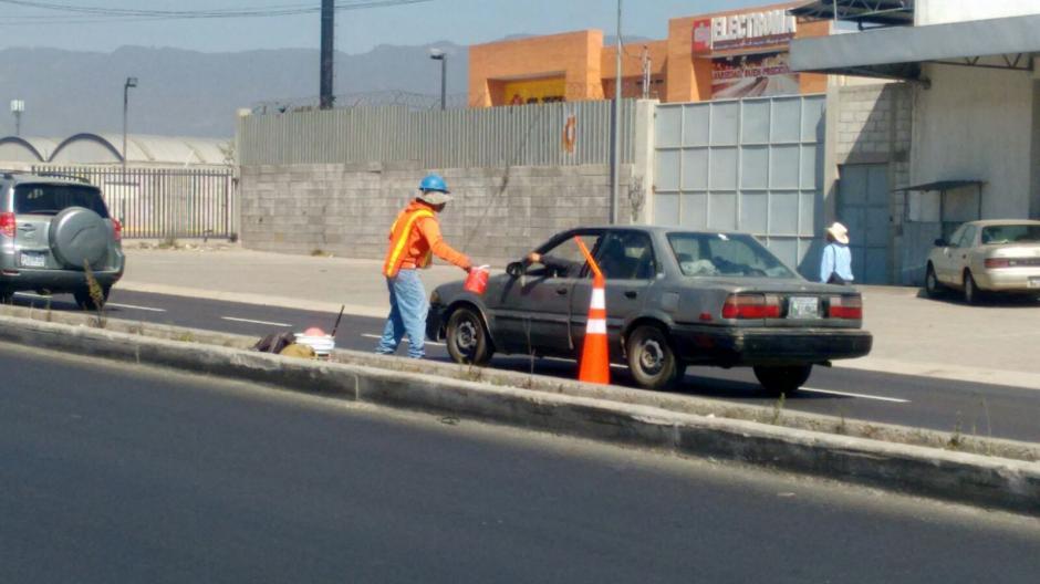 Los automovilistas apoyan a estos jóvenes al señalizar esta vía. (Foto: Carlos González/Stereo100Xela)