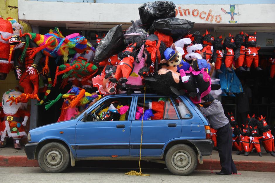 Uno de los vehículos más pequeños que circula en el país se observa atiborrado de piñatas, muchas de ellas para la quema del diablo, y queda lugar solo para el conductor. (Foto: Alexis Batres/Soy502)