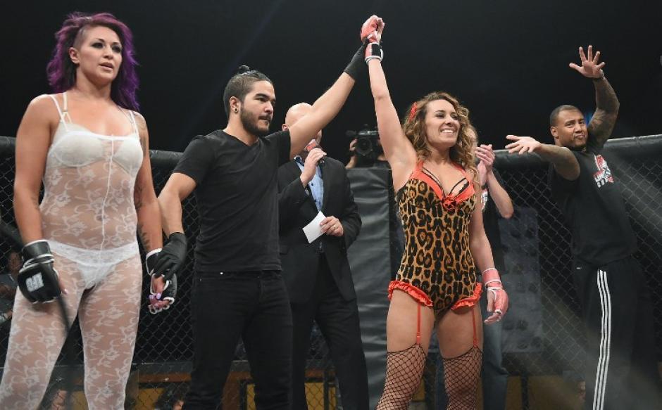 """Jessie """"El Toro"""" Santos observa al árbitro Aron Auruba cuando levanta el brazo triunfante de Allie """"Babydoll"""" Parks en el campeonato de Lucha en Lencería. (Foto: AFP)"""